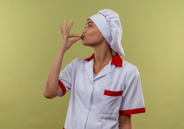 プロフィールビューに立ってコピースペースでおいしいジェスチャーを示すシェフの制服を着た若い料理人の女性