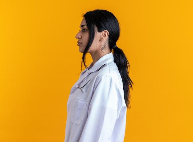 프로필 보기에 서 있는 젊은 여성 의사는 노란색 배경에 격리된 청진기가 달린 의료 가운을 입고 있습니다.