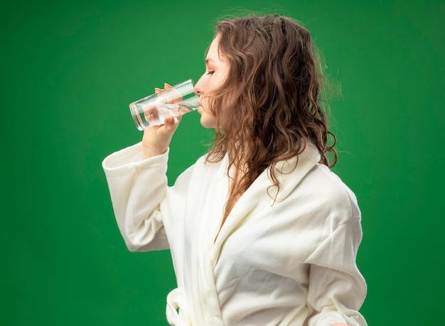 縦断ビューに立って白いローブを着ている若い病気の女の子は緑に分離された水を飲む