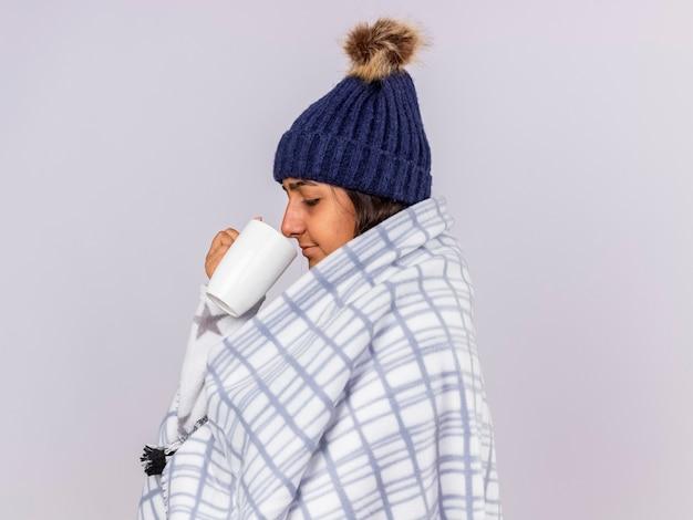 縦断ビューで立っている格子縞の保持に包まれたスカーフと冬の帽子をかぶっている若い病気の女の子