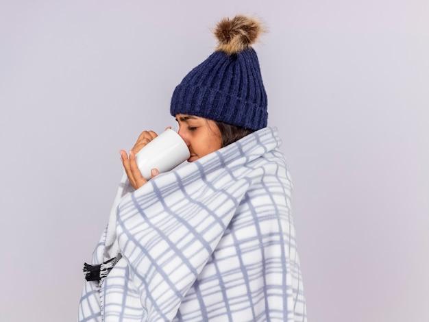 縦断ビューに立って目を閉じてスカーフを包んだ冬の帽子をかぶっている若い病気の女の子