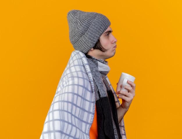 縦断ビューに立って、お茶のカップを保持している格子縞に包まれたスカーフと冬の帽子をかぶっている若い病気の男¡