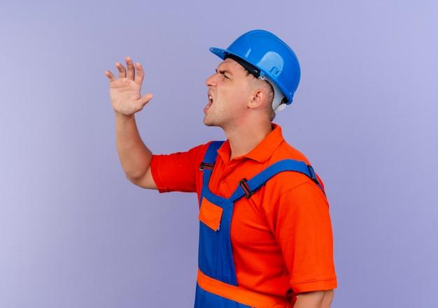 プロフィールビューに立って制服と安全ヘルメットを身に着けている若い男性ビルダーが紫色で誰かを呼び出します