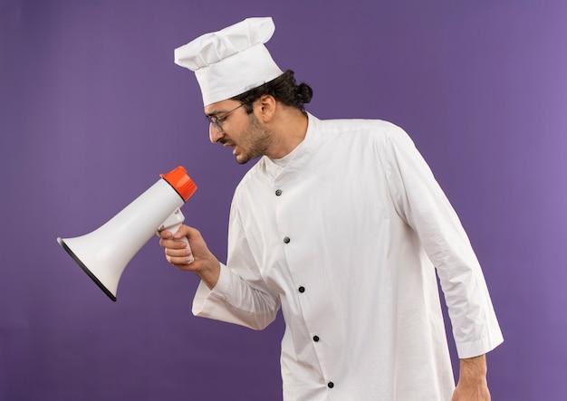 縦断ビューに立ってシェフの制服と眼鏡をかけた若い男性料理人が紫色のスピーカーで話します