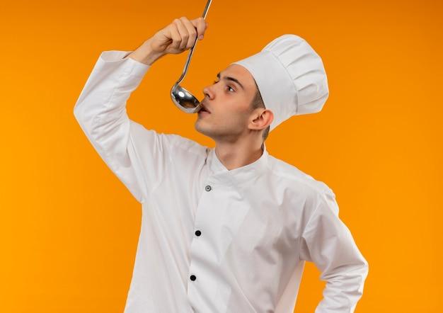 縦断ビューで立っている若い男性のクールな身に着けているシェフの制服お玉からスープを試してみてください
