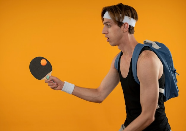 Стоя в профиль, молодой спортивный парень в рюкзаке с повязкой на голову и браслетом, держащим ракетку для пинг-понга, изолированную на оранжевой стене