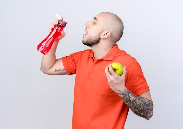縦断ビューに立って白い壁に分離された水のボトルとリンゴを保持している若いスポーティな男