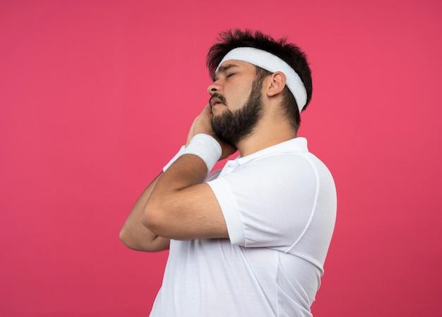 Стоя в профиль, молодой спортивный мужчина с повязкой на голову и браслет показывает жест сна, изолированный на розовой стене