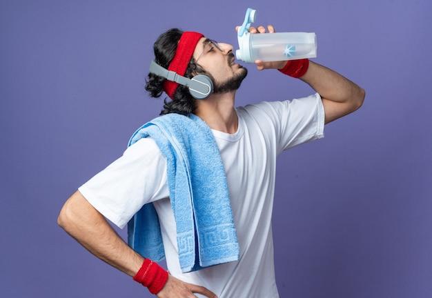 Стоя в профиль, молодой спортивный мужчина с повязкой на голову с браслетом и полотенцем на плече пьет воду