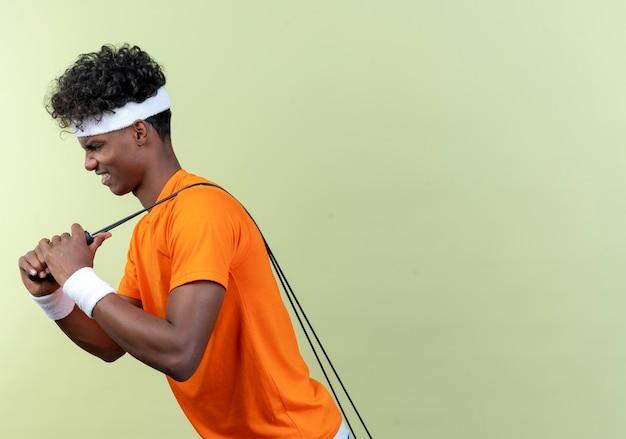 Стоя в профиль, молодой спортивный мужчина с повязкой на голову