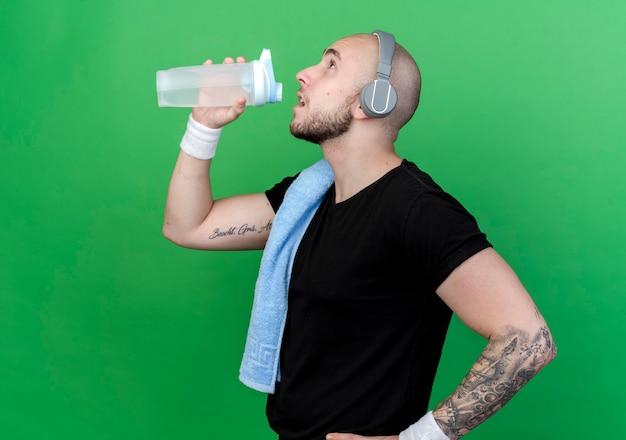 縦断ビューに立ってリストバンドとヘッドフォンを身に着けている若いスポーティな男が緑の壁に隔離された肩にタオルで水筒から飲む
