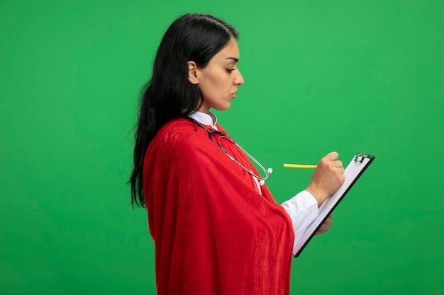 プロフィールビューに立って聴診器で医療ローブを身に着けている若いスーパーヒーローの女の子は、緑に分離されたクリップボードに何かを保持し、書いています
