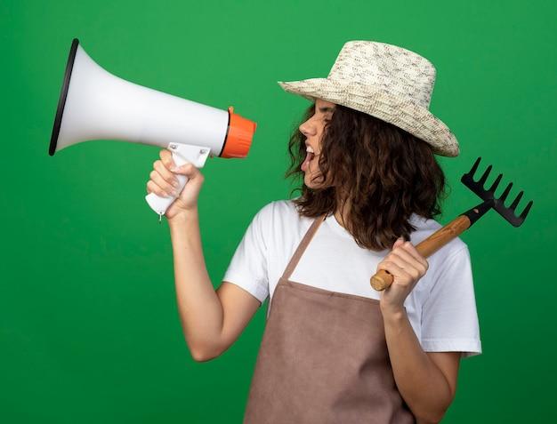 어깨에 갈퀴를 넣어 원예 모자를 쓰고 제복을 입은 프로필보기 젊은 여자 정원사에 서 녹색에 고립 된 확성기에 말한다 무료 사진