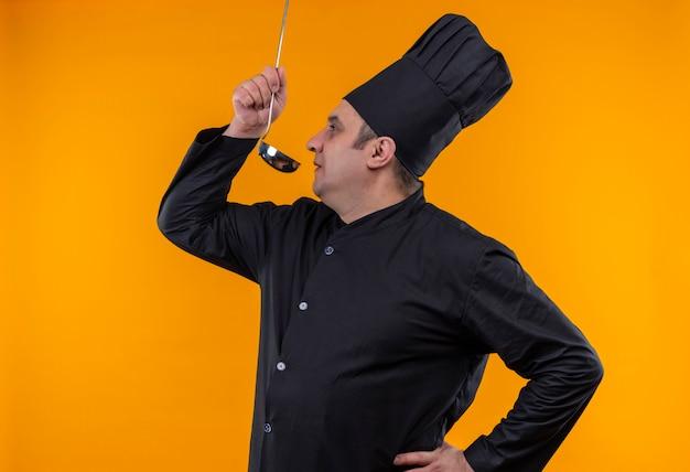 黄色の背景にスープを試してシェフの制服を着たプロフィールviwe中年男性料理人に立って