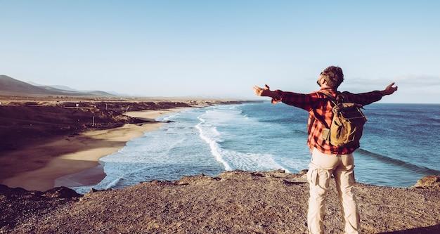 立っている男は、崖の上から野生の美しいビーチの前で自然の屋外の開いた腕を感じます-流行に敏感な人々のための代替のバックパック休暇