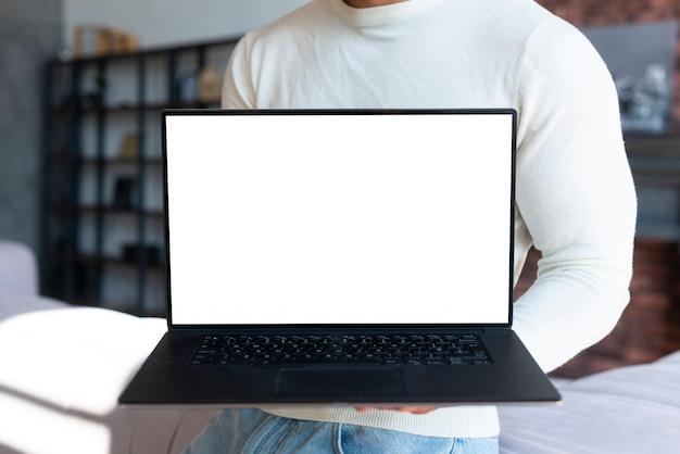 Постоянный мужчина держит ноутбук макет