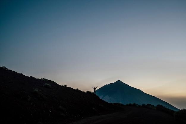 高い山の前に立っている男