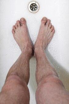 Standing man under shower drain