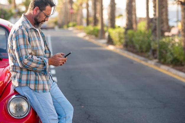 立っている男性は、現代の電話を使って、道路に駐車した美しい赤い車を表示し、旅行地図のオンライン計画の目的地コンセプトのローミングとあらゆる場所でのインターネット携帯電話接続を行います