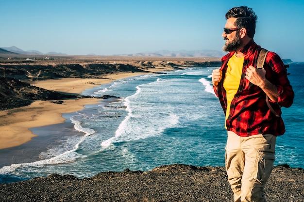 バックパックと美しい野生のビーチとひげを持つ立っている男