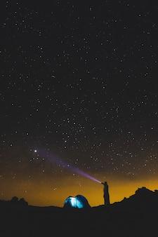 懐中電灯を持った立っている男性が黒い宇宙の夜の銀河を見て、別の休暇旅行で屋外のレジャー活動を楽しんでいます
