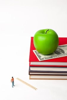 新しい本のスタックにリンゴと立っているミニチュア男