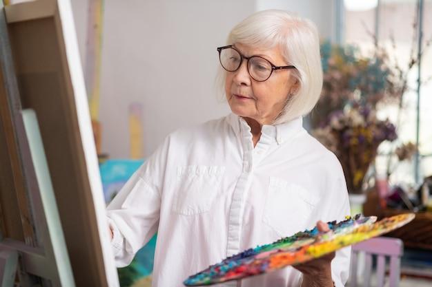 キャンバスの近くに立っています。帆布の近くに立っている眼鏡の絵を着て才能のある引退した女性