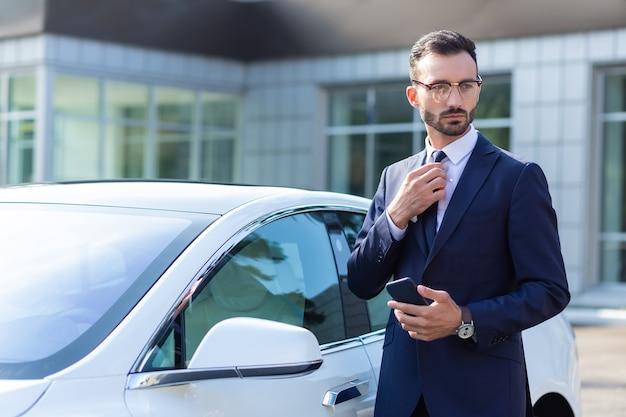 Стоя возле машины. преуспевающий красивый темноволосый бизнесмен в очках стоит возле своей машины