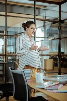 Стоя возле компьютера. занятая беременная женщина, работающая в офисе, стоя возле компьютера и усердно работает