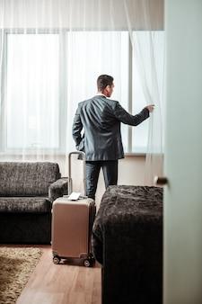 荷物の近くに立っています。窓をのぞきながら彼の荷物の近くに立っている黒い服を着ているビジネスマン