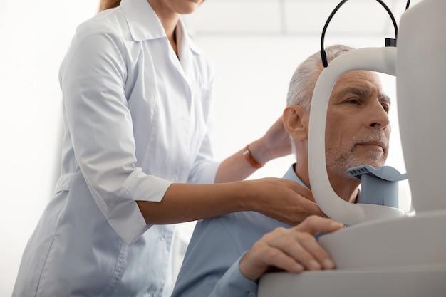 患者の近くに立っています。視力を監視しながら患者の近くに立っている女性の資格のある眼科医