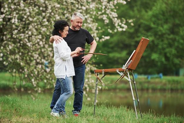 Стоя возле озера. пожилая пара отдыхает и вместе работает над краской в парке