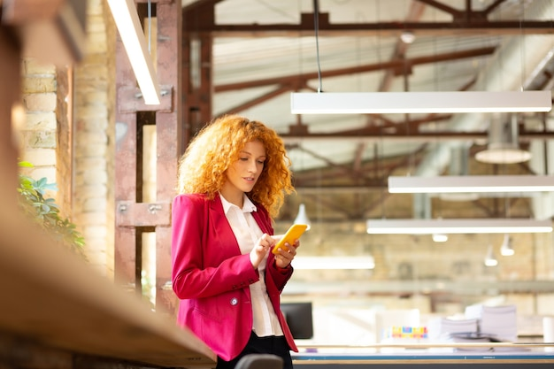 Standing near window. curly red-haired office worker standing near window and using phone