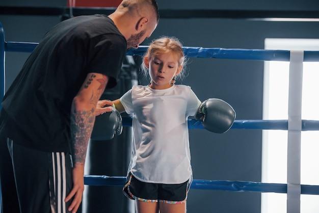 Стоя на боксерском ринге. молодой татуированный тренер по боксу учит милую девочку в тренажерном зале.
