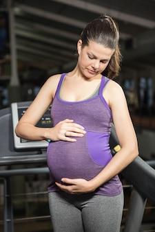 레저 센터에서 배를 만지고 서 임신 한 여자