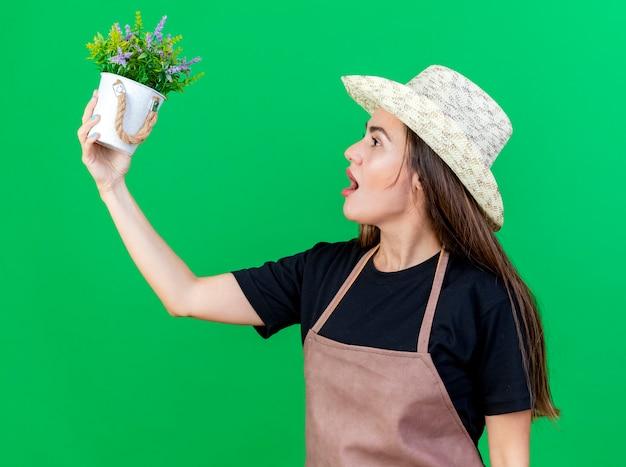 In piedi in vista di profilo bella ragazza giardiniere in uniforme che indossa il cappello da giardinaggio alzando e guardando il fiore in vaso di fiori isolato su verde