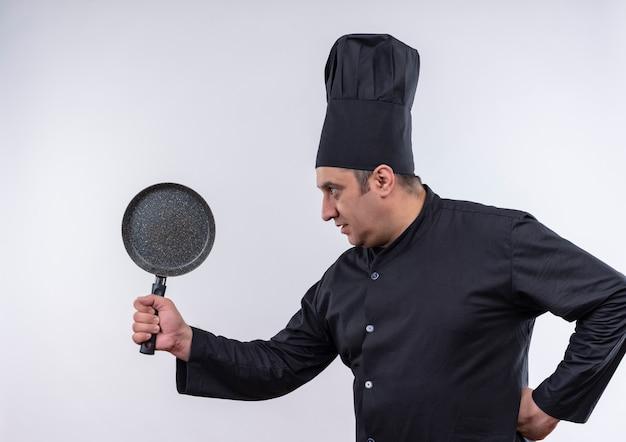 In piedi in vista di profilo maschio di mezza età cuoco in uniforme da chef tenendo la padella mise la mano sul fianco con lo spazio della copia