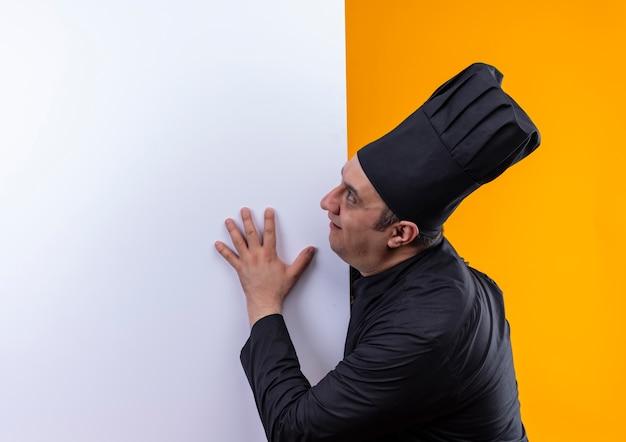 In piedi in vista di profilo cuoco maschio di mezza età in uniforme del cuoco unico che tiene muro bianco su sfondo giallo con spazio di copia