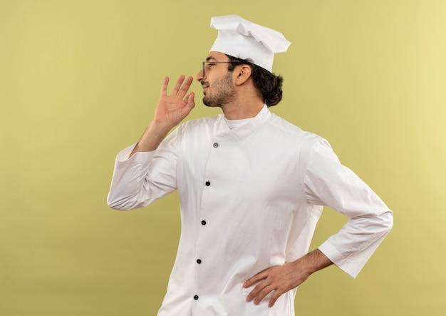 Stando in vista di profilo felice giovane cuoco maschio che indossa l'uniforme del cuoco unico e occhiali che mostrano il gesto delizioso e mettendo la mano sull'anca isolata sulla parete verde