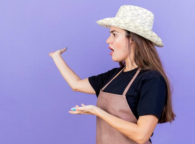Stando in vista di profilo sorpreso bella ragazza giardiniere in uniforme indossando punti di cappello da giardinaggio sul retro isolato su sfondo blu con spazio di copia
