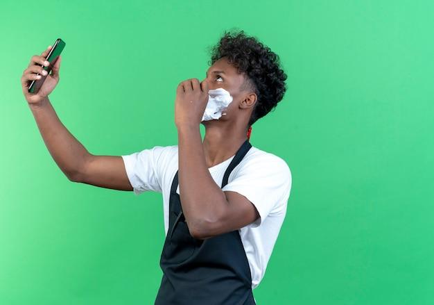 In piedi nella vista di profilo, giovane barbiere maschio afroamericano che indossa un'uniforme con crema da barba applicata sul viso, scatta un selfie
