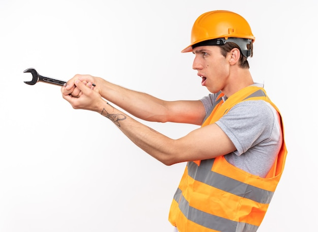Standing in profile view young builder man in uniform holding out open-end wrench at side