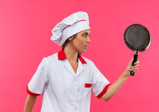 In piedi in vista di profilo giovane femmina cuoco indossando chef uniforme tenendo la padella con lo spazio della copia