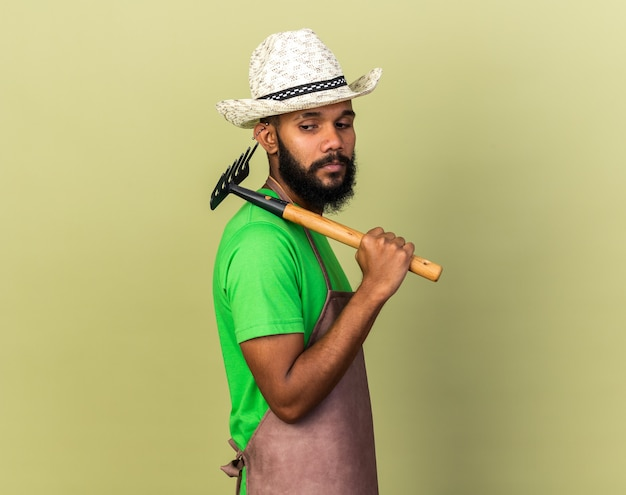 Standing in profile view young gardener afro-american guy wearing gardening hat holding rake on shoulder isolated on olive green wall
