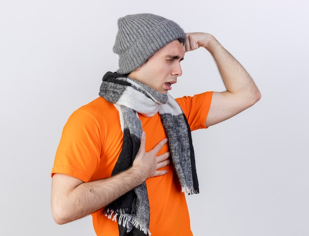 Standing in profile view young ill man wearing winter hat with scarf putting hands on forehead and aching chest isolated on white background