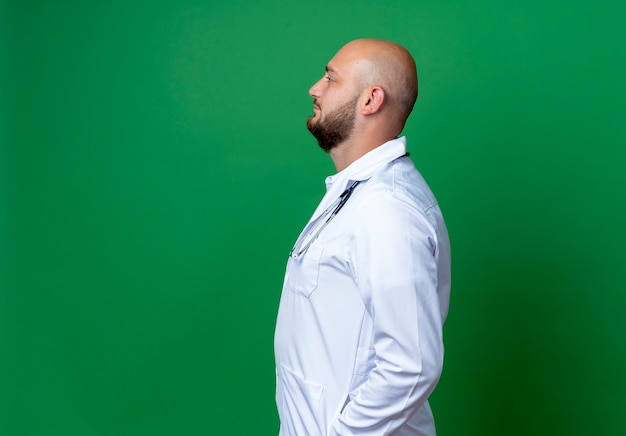 Standing in profile view young male doctor wearing medical robe and stethoscope isolated on green background with copy space