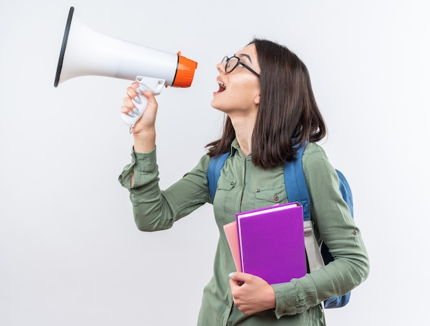 Standing in profile view young school woman wearing glasses with backpack holding books speaks on loudspeaker