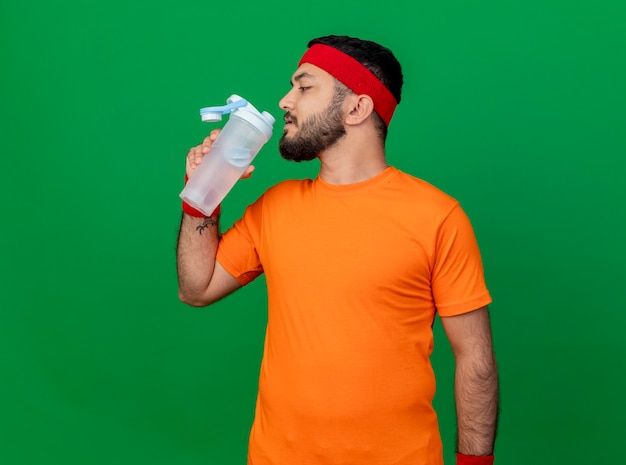 Standing in profile view young sporty man wearing headband and wristband drinks water from water bottle isolated on green background
