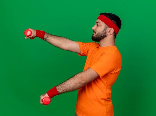 In piedi in vista di profilo giovane uomo sportivo indossa la fascia e il braccialetto che si esercita con i dumbbells isolati su fondo verde