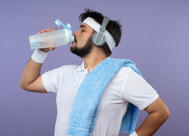In piedi in vista di profilo giovane uomo sportivo che indossa la fascia e il braccialetto con le cuffie beve l'acqua con un asciugamano sulla spalla mettendo la mano sul fianco isolato su verde